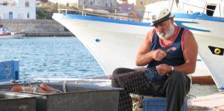 Pescatore artigianale mentre ripara le reti nel porto di Lampedusa. I pescatori con molti anni di esperienza sono osservatori attenti e testimoni preziosi dei cambiamenti ecologici in atto. Foto: Pierpaolo Giordano - ISPRA